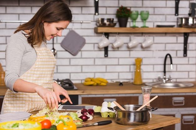 Mulher, usando, tabuleta, enquanto, cozinhar, legumes