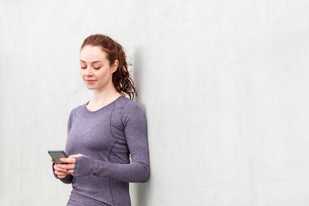Mulher usando telefone celular após a sessão de treinamento