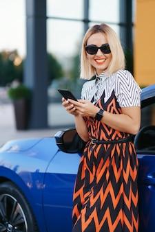 Mulher usando telefone celular, comunicação ou aplicativo online, em pé perto do carro na rua da cidade ou no estacionamento, ao ar livre. compartilhamento de carro, serviço de aluguel