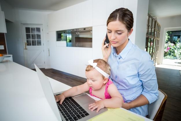 Mulher usando telefone celular e menina brincando com o laptop