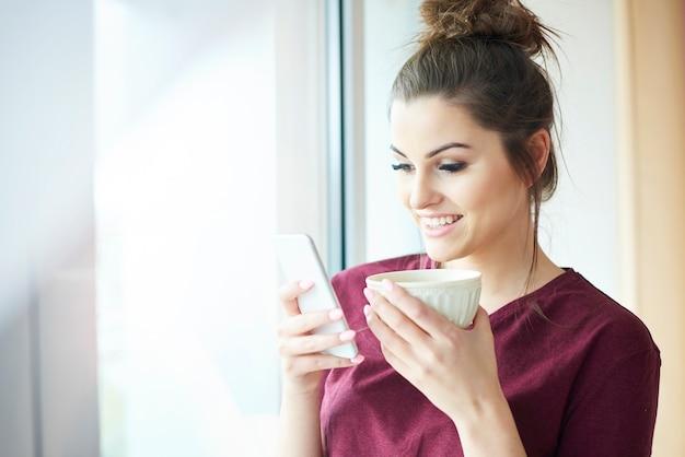 Mulher usando telefone celular enquanto bebe café