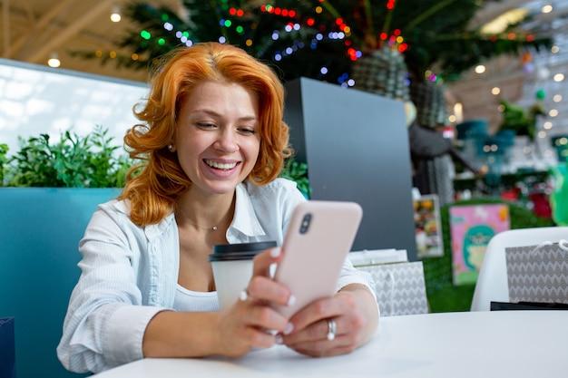 Mulher usando telefone celular enquanto bebia café no shopping