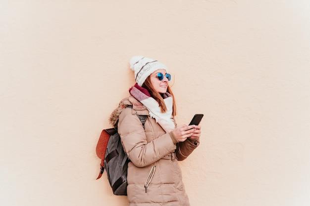 Mulher usando telefone celular na parede amarela. tecnologia e conceito de inverno