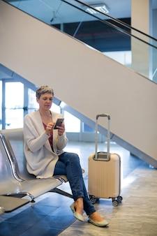 Mulher usando telefone celular na sala de espera