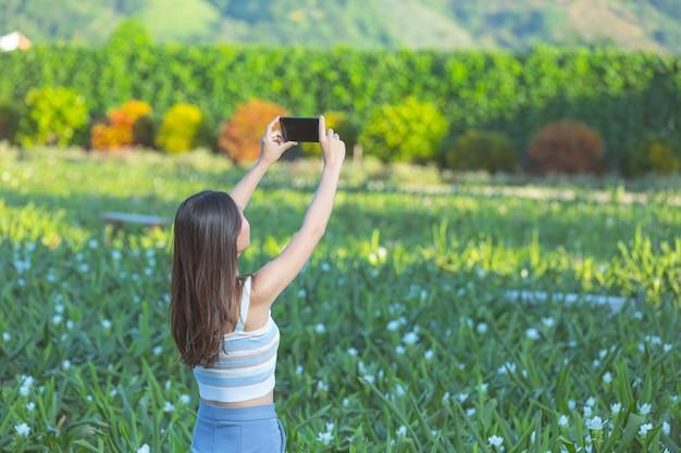 Mulher usando telefone celular para tirar foto no jardim de flores.