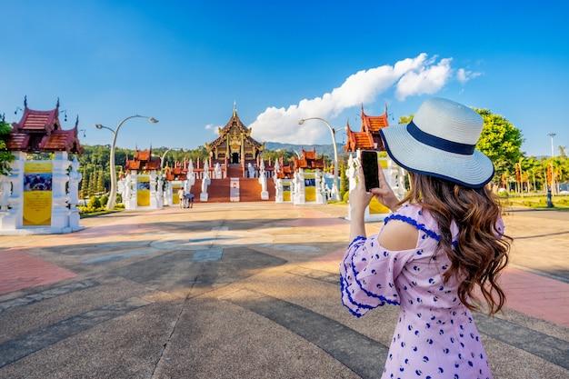 Mulher usando telefone celular tira uma foto no ho kham luang estilo tailandês do norte no royal flora ratchaphruek em chiang mai, tailândia.