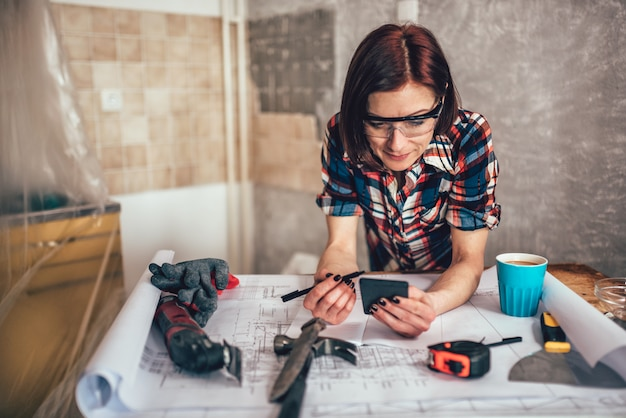 Mulher usando telefone inteligente durante a reforma da cozinha