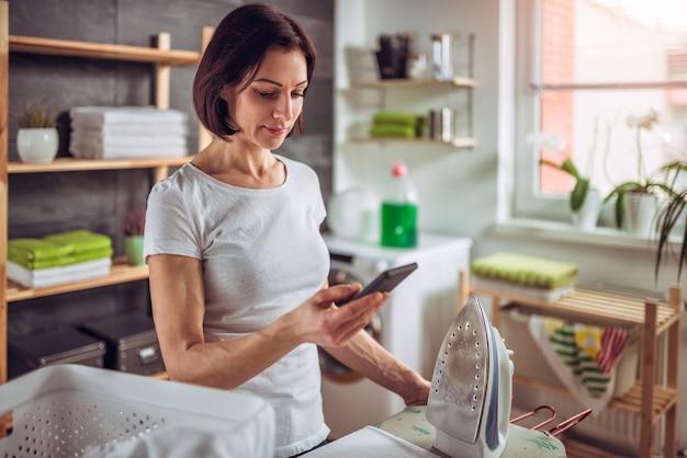 Mulher usando telefone inteligente enquanto passando roupas