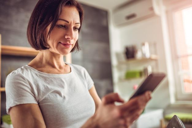 Mulher usando telefone inteligente na lavanderia