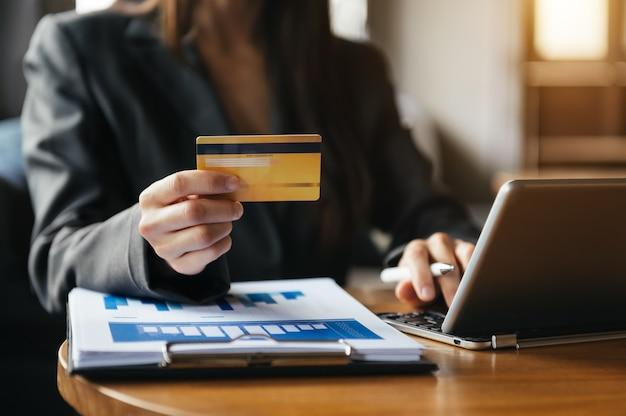 Mulher usando telefone inteligente para pagamentos móveis, compras online, omni channel, sentada na mesa, tela de interface gráfica de ícones virtuais na luz da manhã