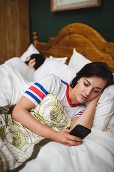 Mulher, usando, telefone móvel, enquanto, encontrar-se cama
