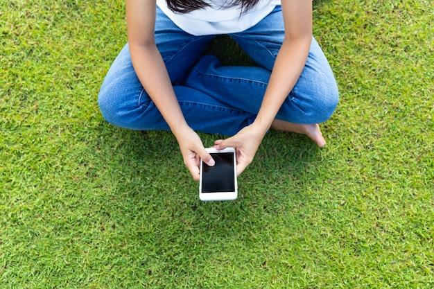 Mulher usando telefone móvel esperto na grama para relaxar com as mídias sociais