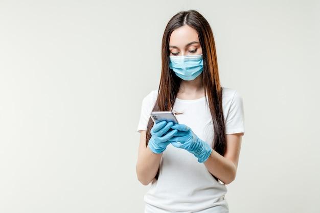 Mulher usando telefone usando máscara e luvas