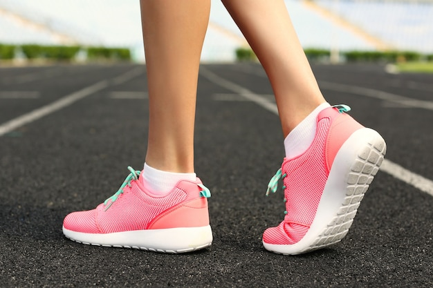 Mulher usando tênis rosa em um estádio de corrida