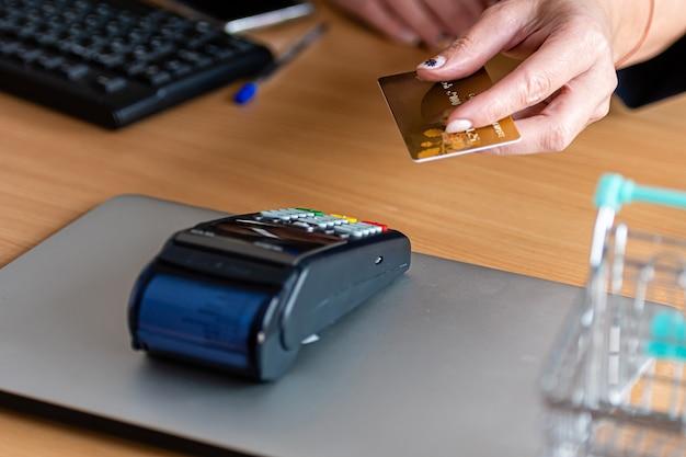 Mulher usando terminal de cartão de pagamento para fazer compras online com cartão de crédito, leitor de cartão de crédito, conceito financeiro
