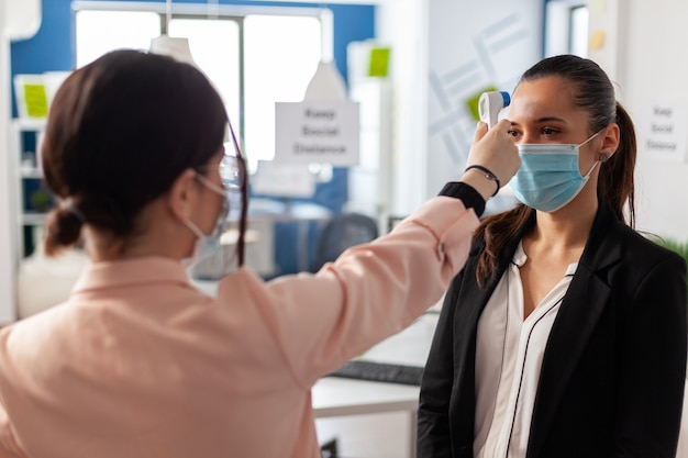 Mulher usando termômetro infravermelho, medindo a temperatura do trabalhador de escritório, durante a epidemia global de coronavírus em uma empresa de negócios. novo normal em tempo de pandemia mundial com covid19.