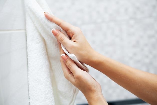 Mulher usando toalha para limpar as mãos secas após a lavagem