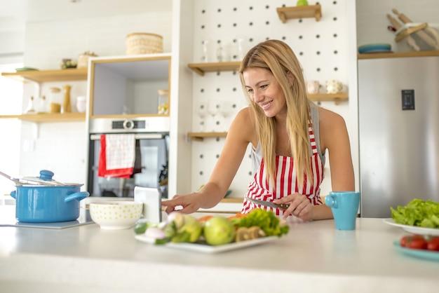 Mulher usando um avental branco com linhas vermelhas olhando para o dispositivo e cozinhando algo