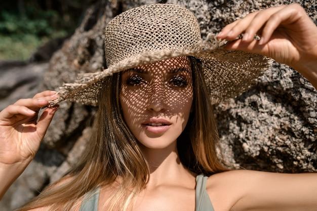 Mulher usando um chapéu de palha e sorrindo. retrato de uma jovem feliz em biquíni, olhando para a câmera