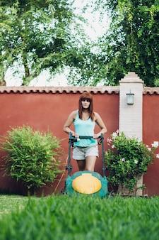 Mulher usando um cortador de grama em um jardim na espanha