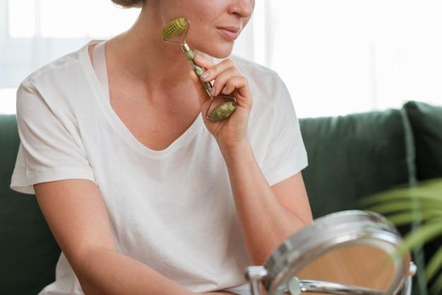 Mulher usando um dispositivo para massagem no rosto