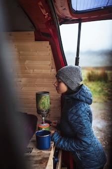 Mulher usando um fogão portátil de acampamento para ferver água