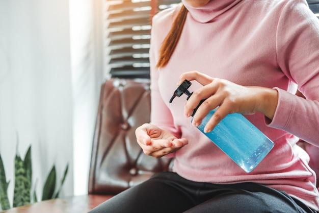 Mulher usando um gel de álcool desinfetante para as mãos para lavar as mãos para evitar vírus e doenças em casa