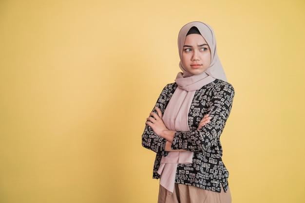 Mulher usando um hijab zangada com ciúmes com os braços cruzados em pé