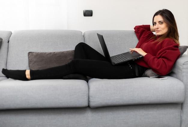 Mulher usando um laptop enquanto relaxa no sofá