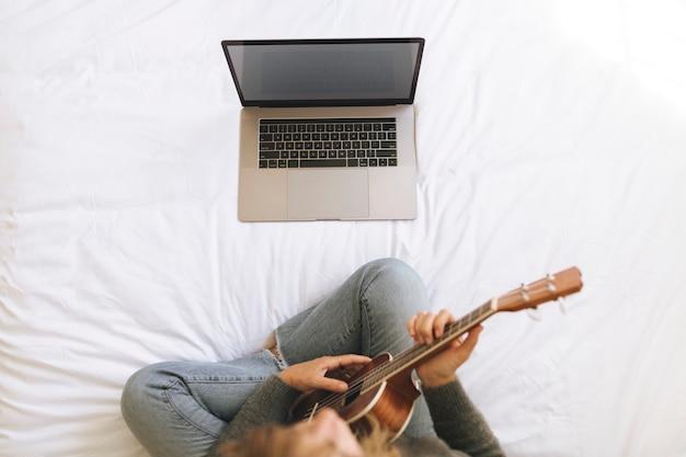 Mulher usando um laptop enquanto toca cavaquinho durante o bloqueio