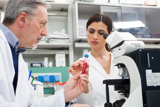 Mulher, usando, um, microscópio, em, um, químico, laboratório