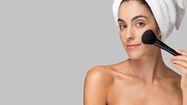 Mulher usando um pincel de maquiagem copiar espaço