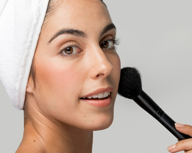 Mulher usando um pincel de maquiagem