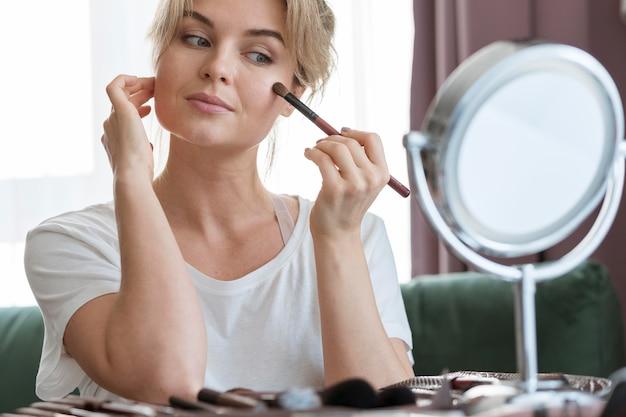 Mulher usando um pincel e olhando no espelho