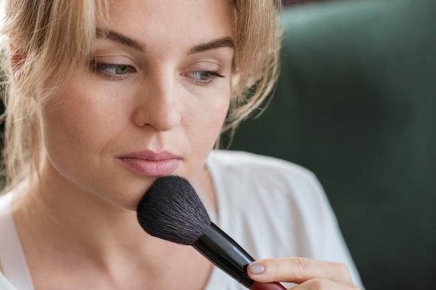 Mulher usando um pincel para a maquiagem