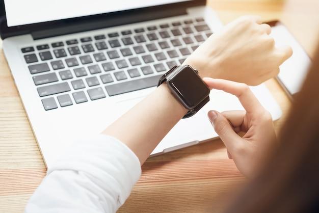 Mulher usando um relógio digital no visor e tecnologia avança na comunicação.