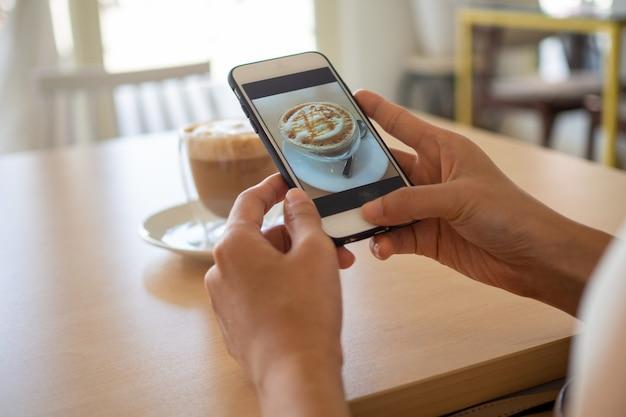 Mulher usando um smartphone para tirar foto de um café
