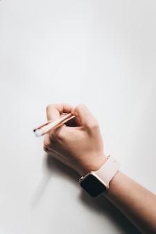 Mulher usando um smartwatch escrevendo em um papel