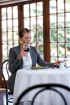 Mulher usando um tablet e bebendo vinho