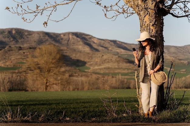 Mulher usando um telefone inteligente em um campo verde