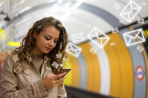Mulher, usando, um, telefone móvel, ligado, a, tubo, estação subterrânea, londres