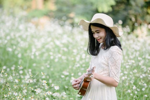 Mulher usando um vestido branco bonito e tocando ukulele