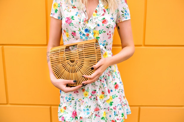 Mulher usando um vestido floral e segurando um saco de palha, se passando perto da parede amarela