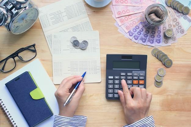Mulher usando uma calculadora e segurando canetas na mesa