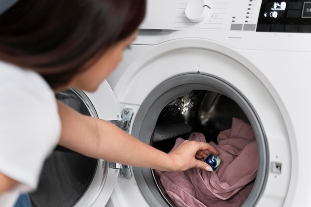 Mulher usando uma cápsula para lavar a roupa