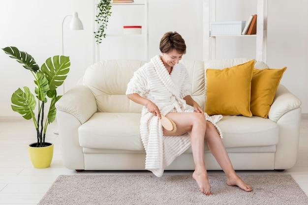 Mulher usando uma escova na perna em tiro longo