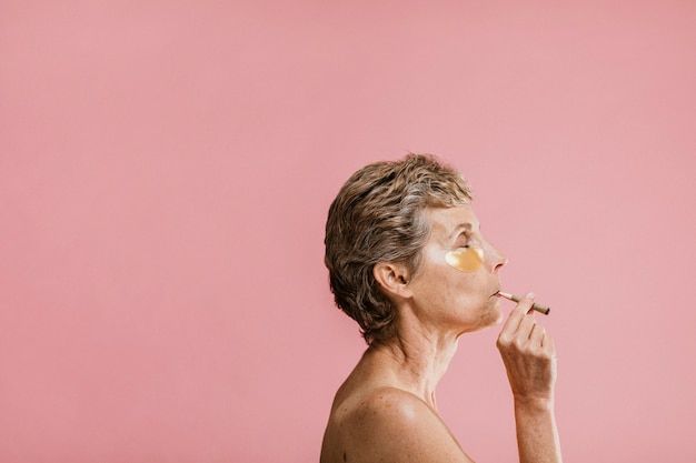 Mulher usando uma máscara dourada e fumando charutos