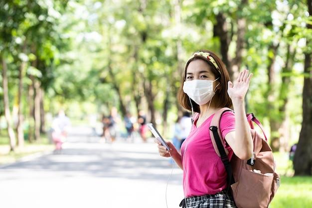 Mulher usando uma máscara facial com mãos acenando para cumprimentar a amiga e usando o smartphone para ouvir música ao ar livre em um parque verde exuberante