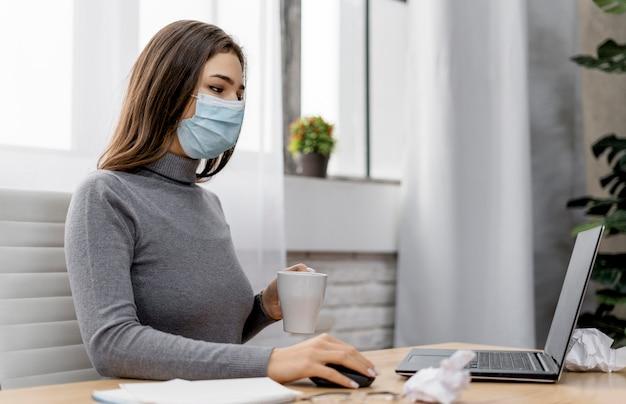 Mulher usando uma máscara médica enquanto trabalha em casa