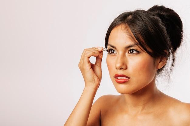 Mulher usando uma pinça nas sobrancelhas